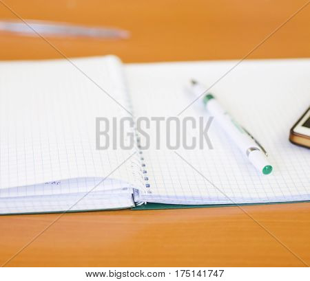 Notebook and pen for writing lectures on a brown background