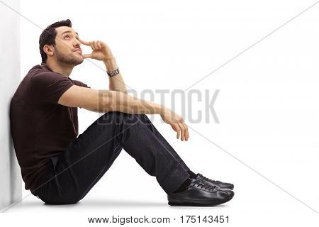 Pensive young man sitting on the floor and looking up isolated on white background