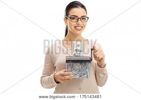 Young woman destroying a dollar banknote in a paper shredder isolated on white background