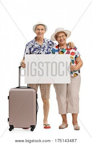 Full length portrait of mature tourists with a suitcase holding a blank signboard isolated on white background
