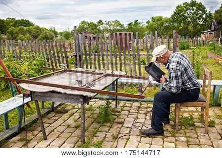 Aged man welding metal structure at his dacha