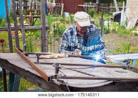 Elderly man welding metal structure at the garden