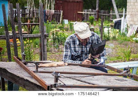 Elderly man welding metal construction at the garden