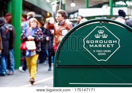 London UK - February 10 2017 - Floor signage stand of Borough Market with walking tourists in the background
