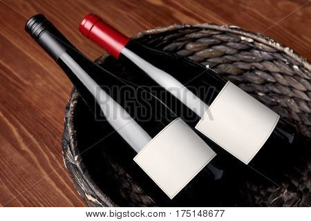 Wooden basket with two bottles of red wine. Top view