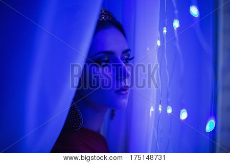 Girl eastern brunette in a red dress with beautiful hairstyle earrings of beads and a crown on her head and bright makeup. Female eastern style. Mysterious eastern woman. Blue light