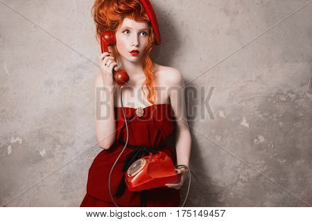 Redhead curly surprised girl in a red beret her lips smeared red lipstick and holding a disk telefon. A surprised woman in a red dress on a gray background. Retro lady surprised. Photo in theater actress. Retro film. Art photo