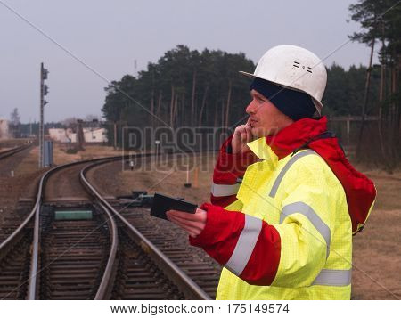 Railroad Worker, Engineer In Protective Work Wear And Helmet Talking By The Phone. Railroad Tracks O