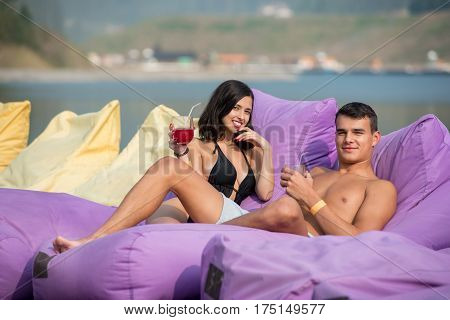Happy Man And Woman Are Enjoying Each Other's Company With Drinks On The Soft Loungers At Luxury Res