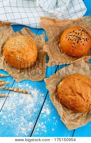 Assortment of multi-grain bread rolls on on blue wooden table. Home made bread.