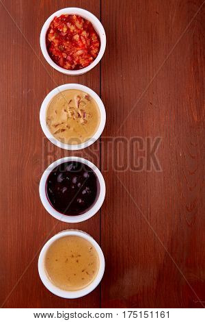 Sauces ketchup, mustard, mayonnaise, sour cream, soy sauce in clay bowls on wooden background. Food concept. Top view