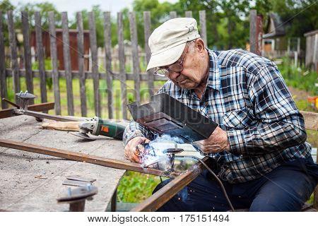 Senior man welding metal construction at his garden
