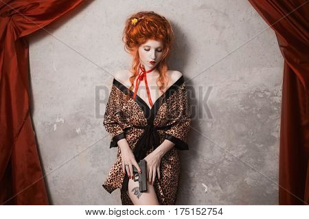 A  pinup woman with red hair in leopard print gown with a gun in his hand. Red-haired pinup girl with pale skin and blue eyes with a bright unusual appearance with a red ribbon around her neck. French  pinup courtesan.  Pinup model