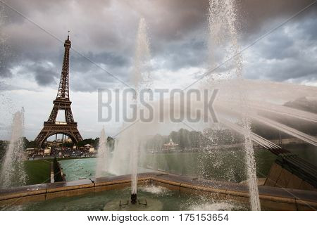 Fountain in Paris at the Trocadero square near the Palace of Chaillot. Travel through Europe. Attractions in France. The gray sky above the Eiffel Tower and fountain