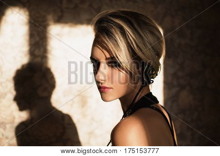 Lovely girl with tanned skin and white hair listening to music on headphones. Female beauty portrait of a beautiful makeup. Enjoying good music in headphones