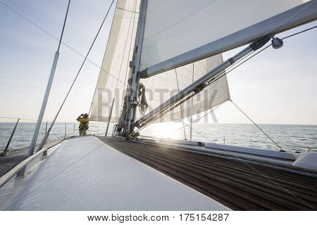 Man Standing On Front Of Sail Boat Deck In Sea