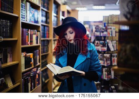Woman with book and red curly hair in blue coat on background of book shop. Red-haired girl with pale skin and bright appearance with black hat on head and book. Street style. Read book