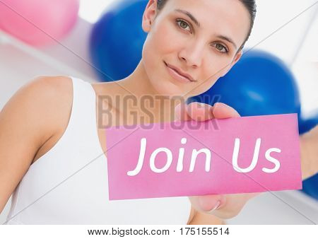 Portrait of fit woman showing join us card in fitness studio