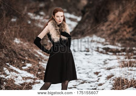 Striking redhaired girl with long red hair in black clothes. Woman in black dress and fur around neck with long black gloves posing on background of winter nature. Female street style. Beautiful elegant redhaired model