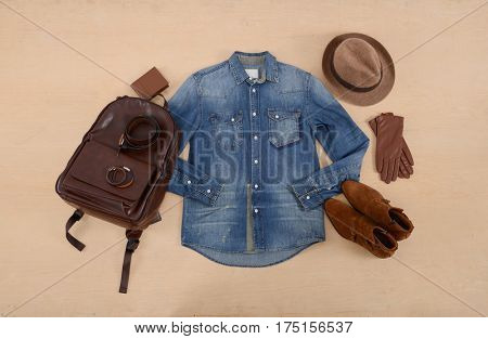 men's casual fashion with jeans shirt, handbag ,gloves, hat,on wooden