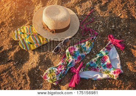 Sunglasses with hat on sand. Colorful swimsuit and flip flops. Style of summer. Get away from the bustle.
