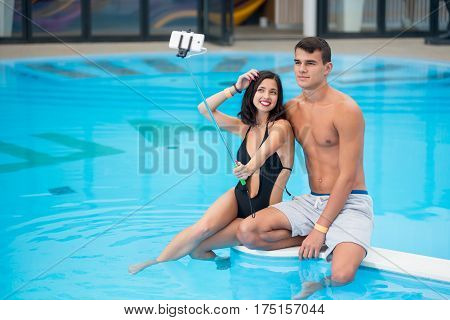 Young Pair - Man And Woman Sitting By The Pool With Perfect Aqua Water And Making Selfie Photo On Th