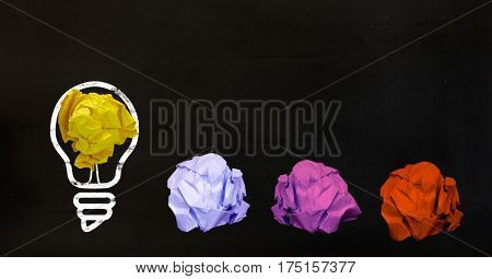 Conceptual image of bulb with multi colored crumpled paper on black background