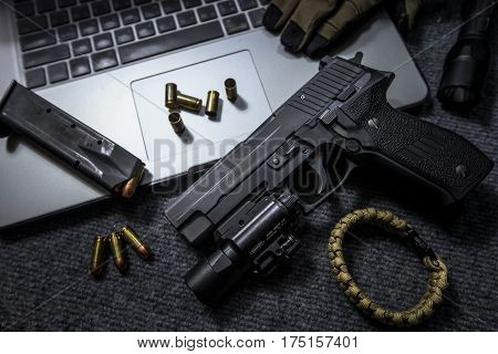 handgun or pistol and labtop on the table
