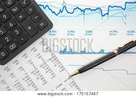 Financial accounting. Stock market graphs and charts analysis. Pen and calculator on business reports