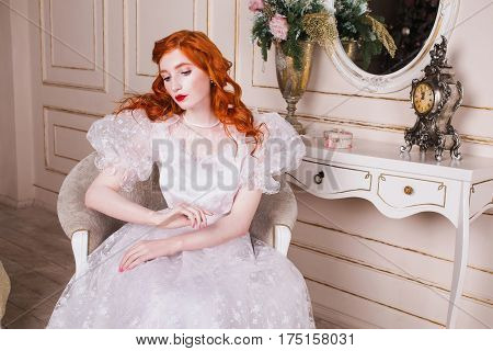 Luxury woman with long red curly hair in a white vintage  luxury wedding dress with white pearl earrings on her ears. Red-haired  luxury girl with pale skin blue eyes a bright unusual appearance in the luxurious bedroom