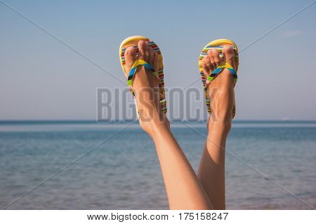 Female legs and sea. Feet in colorful flip flops. Away from bustle and noise. Get a tan.