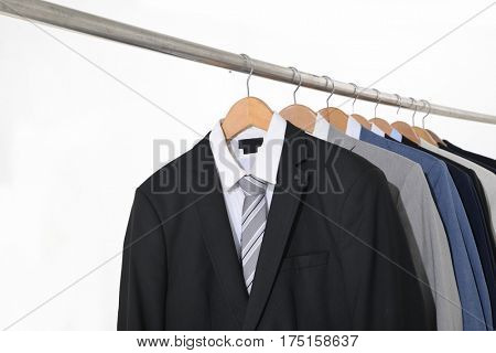 Set of men's suits hanging-white background