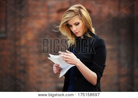 Young business woman reading a tax letter on city street. Stylish fashion model in black jacket outdoor