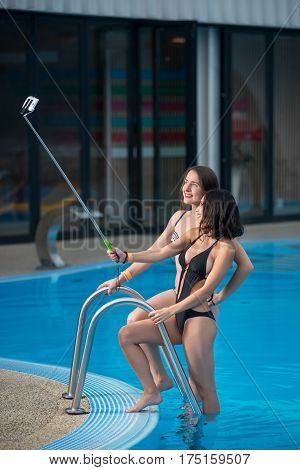 Two Attractive Females In Bikini Posing Against The Swimming Pool With Perfect Aqua Water And Making