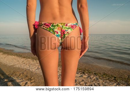 Woman's butt on sea background. Body of a young woman. Beauty and warmth. Get fit for summer.