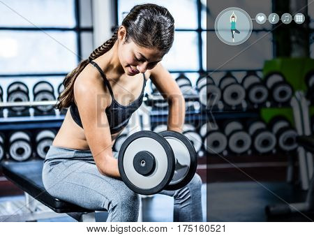DIgital composition of woman working out with dumb bells against digital interface in gym