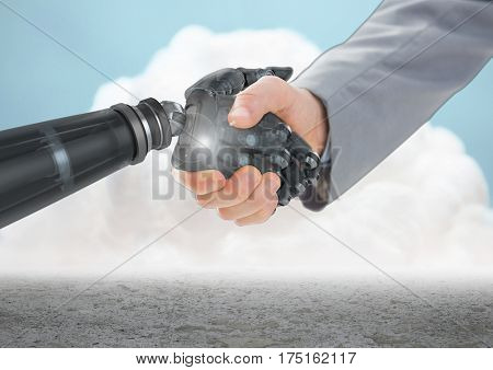 Digital composition of businessman shaking hands with robot hand with clouds in background
