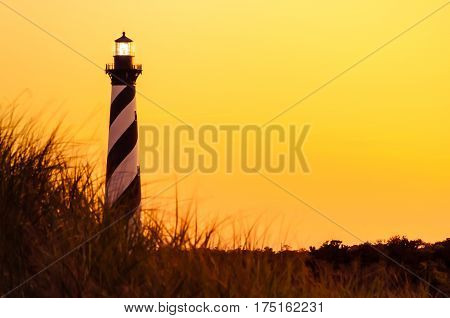 The Cape Hatteras lighthouse lit up at sunset