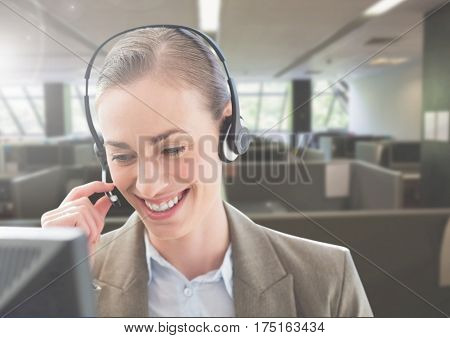 Smiling customer service woman talking on headphone in office