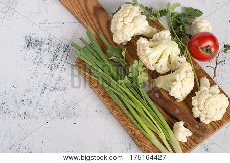 Fresh vegetables. Cauliflower, green onion, parsley sprigs, red ripe tomato and a knife on the kitchen cutting board.