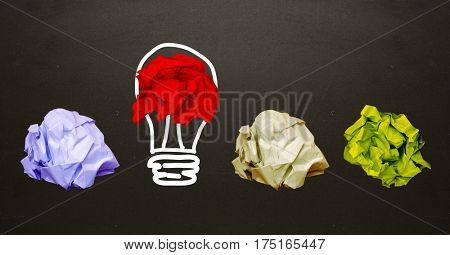 Close-up of crumpled papers with light bulb shape on black background