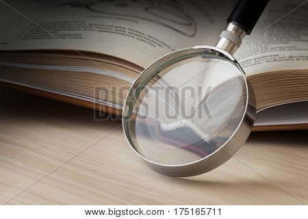 Open book and a magnifying glass in dark tones. The concept of study research/