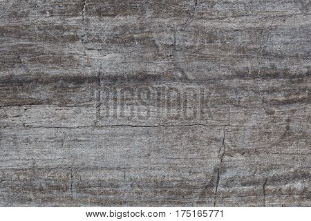 Texture of a brown-gray stone with cracks closeup