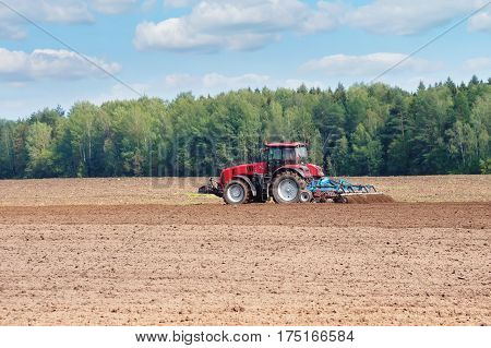 Rural landscape. The tractor in the field cultivates the earth.