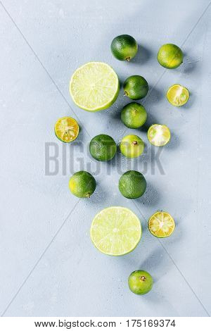 Whole, sliced lime and mini limes over gray stone texture background. Top view, space