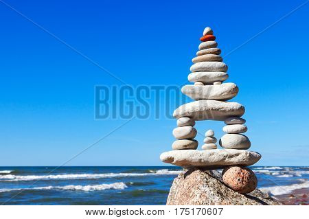 High pyramid of white stones balance on the edge of the cliff on the sea background. Concept of harmony and balance