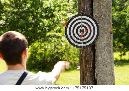 man throwing darts at a target. the goal is attached to the tree in the park