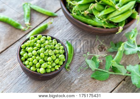 young peas in a clay plate on a wooden table. standing next to a plate of pea pods. next to the plates is the stalk of peas.