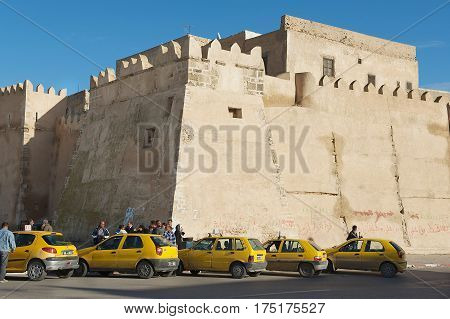 SFAX, TUNISIA - NOVEMBER 30, 2011: Taxis wait for passengers in from of the medina wall in Sfax, Tunisia.