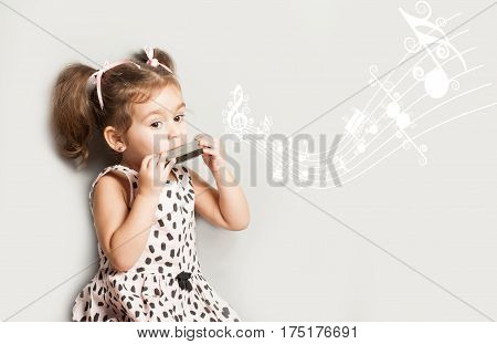 Cute little girl playing harmonica isolated on white. music education concept